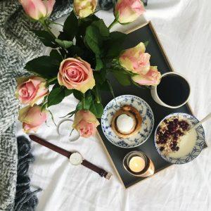 Morgenmad og blomster på sengen